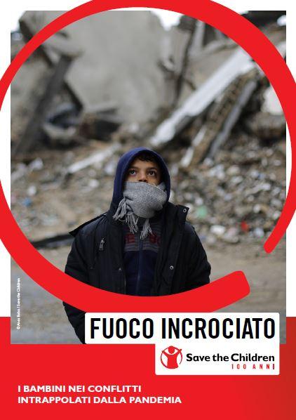 copertina del report dal titolo 'fuoco incrociato' con bimbo siriano in copertina in mezzo alle macerie.