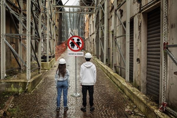 ragazzi in piedi di spalle davanti a un cartello di divieto