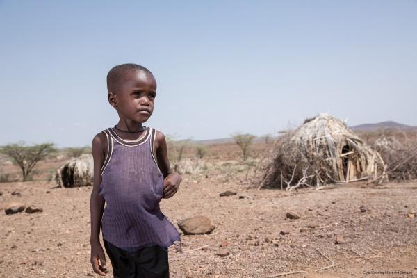 bambino etiope in piedi in una zona arida guarda l'orizzonte