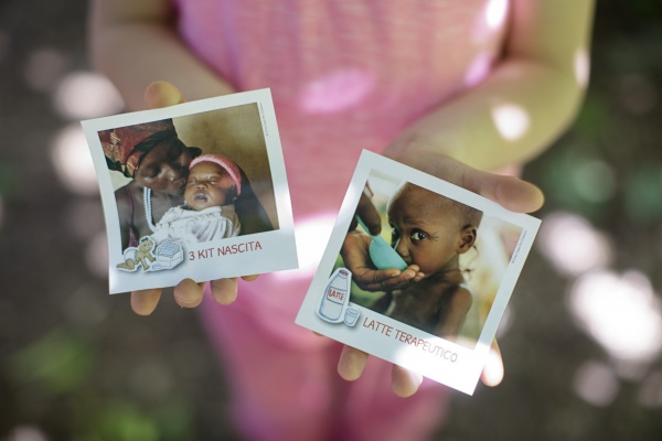 bambina mostra le cartoline di auguri da regalare kit nascita e latte terapeutico
