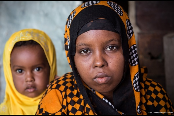 Aisha posa in primo piano insieme alla figlia, entrambe indossano un velo colorato dai colori giallo e nero.