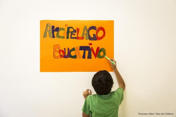 bambino di spalle colora un cartellone giallo appeso al muro con la scritta 'arcipelago educativo'