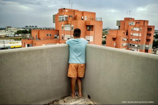 bambino su un balcone di spalle in piedi guarda gli edifici arancioni davanti a sè