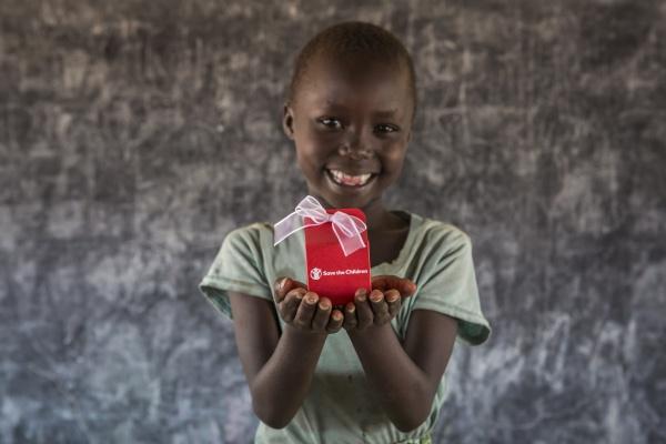 bambina_africana_sorridente_mostra_scatolina_portaconfentti_Save_the_Children