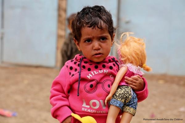 bambina con indosso un maglioncino rosa tiene una bambola in braccio