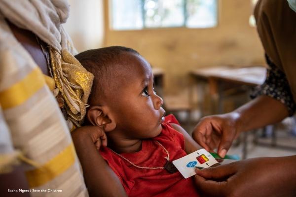 bimbo in braccio alla mamma che guarda l'operatore che gli sta misurando la circonferenza del braccio con il MUAC il braccialetto per misurare lo stato di nutrizione