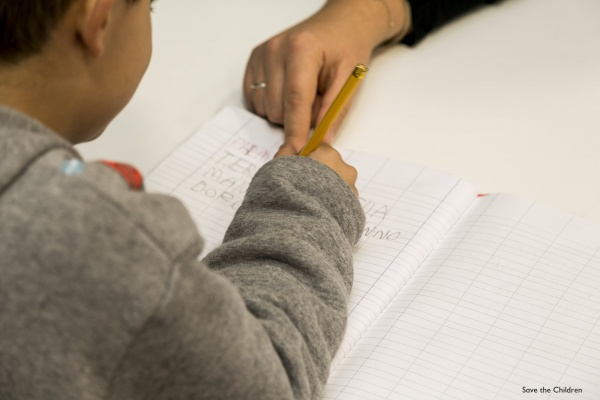 dettaglio su bambino che scrive su un foglio