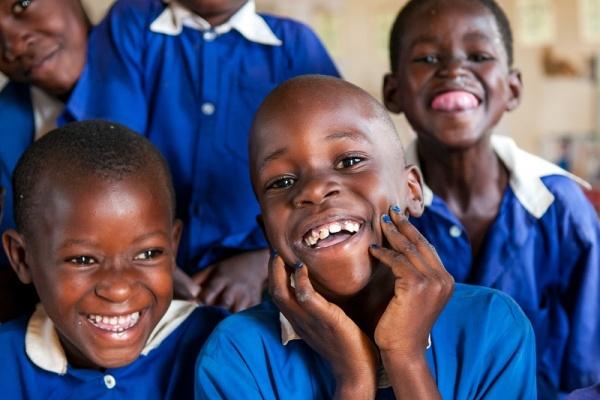 quattro bambini ugandesi sorridenti. Vestiti in divisa scolastica blu.