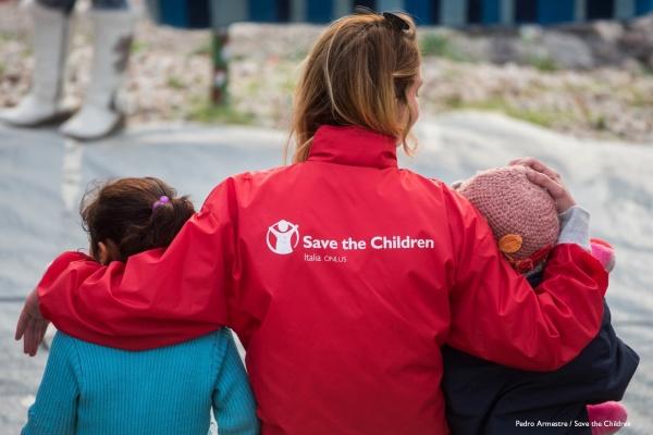 operatrice save the children di spalle con giubbotto rosso tiene sottobraccio due bambini