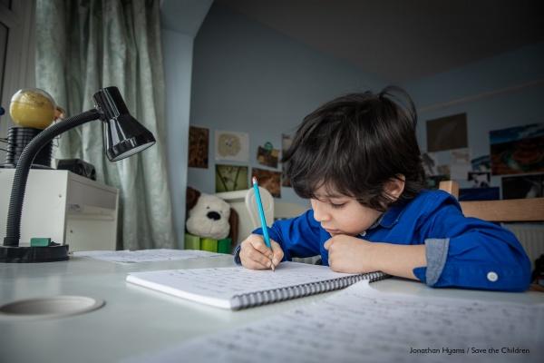 bambino alla scrivania di casa che scrive alla luce di una lampada