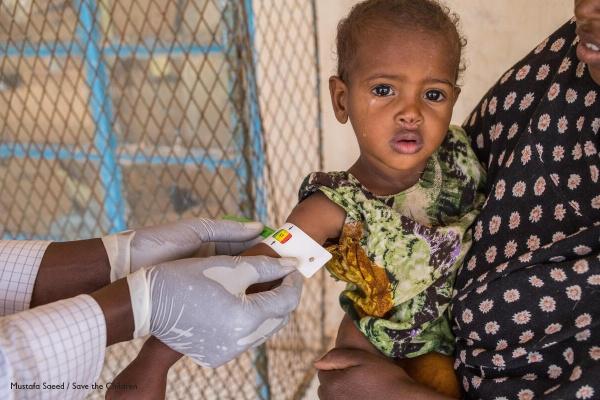 bimbo in braccio alla mamma mentre un operatore gli misura la circonferenza del braccio per determinarne lo stato di nutrizione