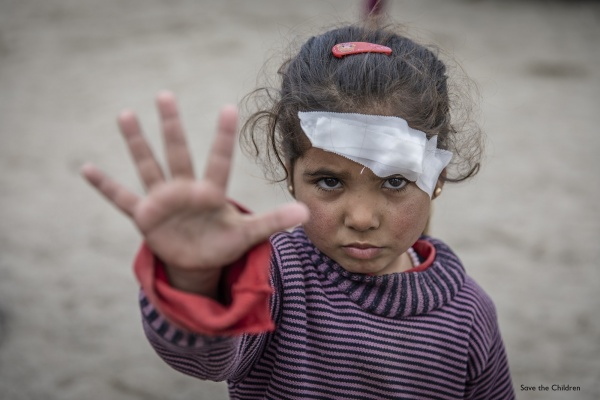 bambina in primo piano con fascia medica sul capo con mano aperta a segno di stop