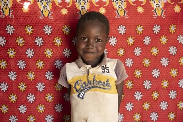 Bambino kenyota posa per una foto a mezzo busto davanti a uno sfondo rosso.