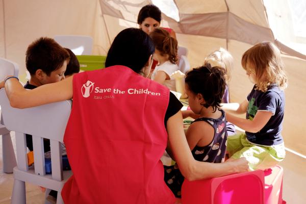 operatrice di save the children insieme ad alcuni bambini durante un attivita