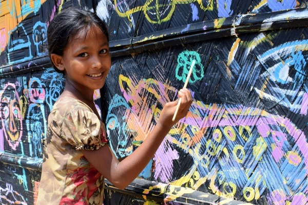 bambina felice dipinge su una parete