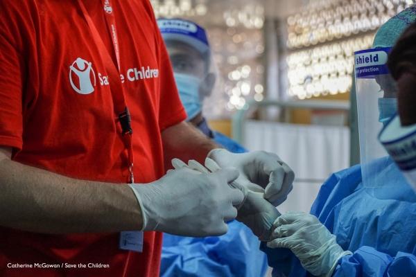 dettaglio su mani con guanti di un operatore save the children con maglietta rossa e di una dottoressa con camice blu e protezioni per coronavirus