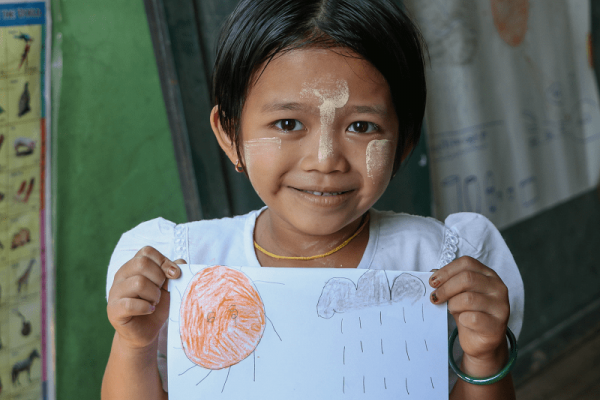 Bambina del Myanmar mostra il disegno che ha appena fatto.