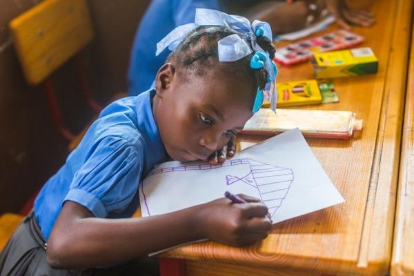 Bambini haitiana, in divisa scolastica blu, seduta al banco di scuola disegna.