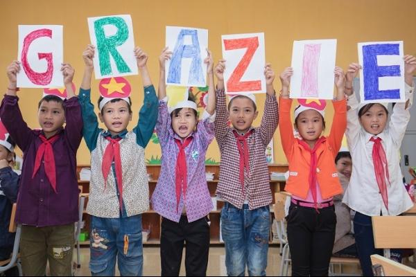 6 bambini nepalesi in piedi tengono le lettere per formare la parola grazie