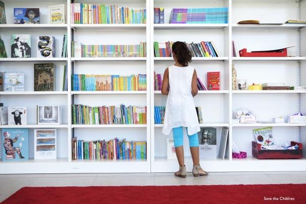 bambina in piedi davanti a una libreria all'interno di un punto luce