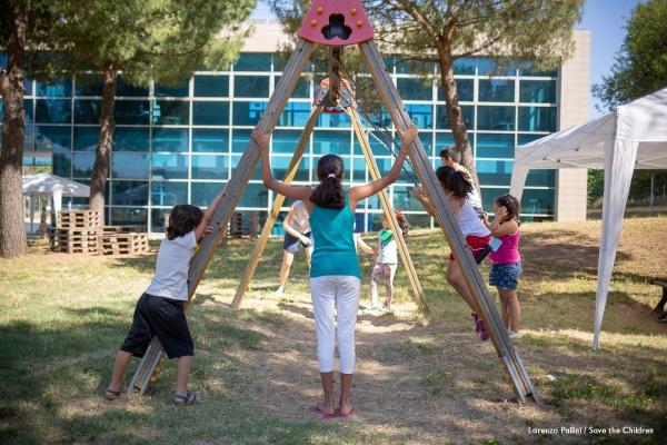 bambini che giocano intorno ad un'altalena nel parco del Punto Luce di Torre Maura