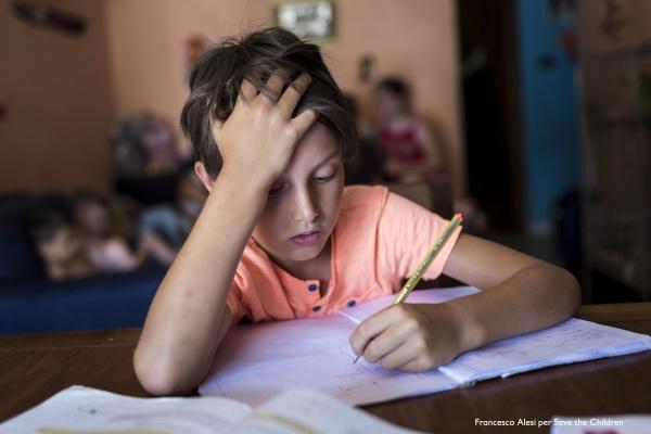 bambino seduto alla scrivania mentre scrive su un foglio bianco