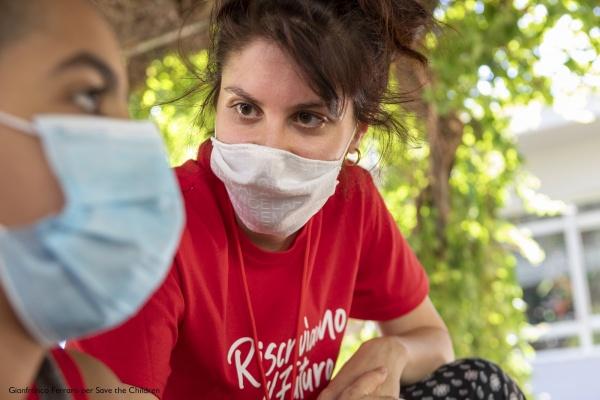 operatrice save the children con maglietta rossa e mascherina mentre parla con un ragazzo con mascherina