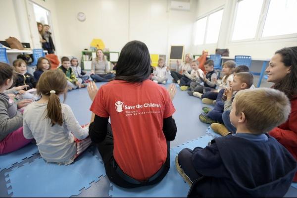 operatrice save the children Italia di spalle in cerchio con dei bambini durante un attività in post emergenza