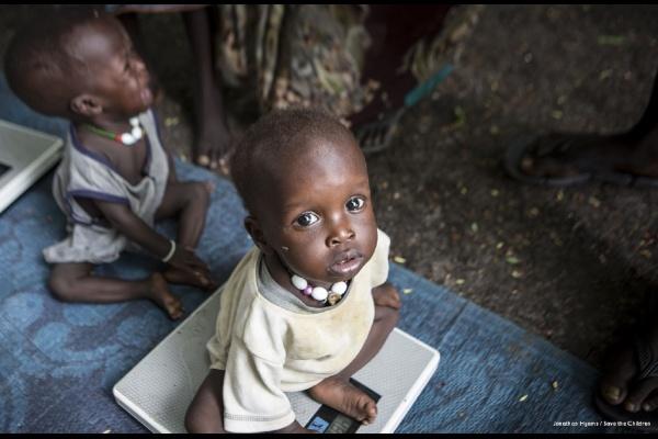 Due bambini neri seduti su una stuoia blu uno dei due su una bilancia e guarda in camera