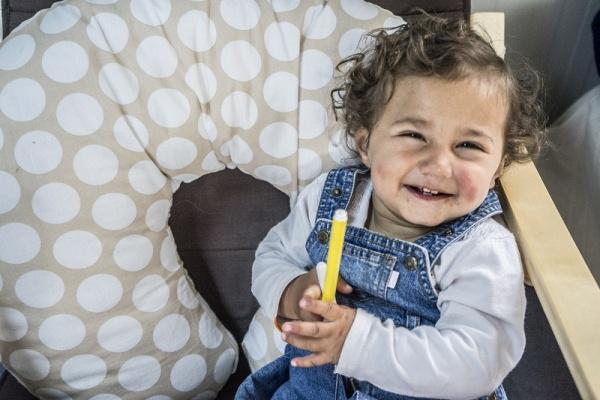 Bambina siriana sorridente con un pennello giallo in mano