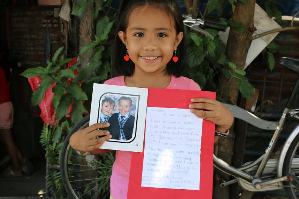 Una bambina filippina mostra la lettera che ha ricevuto dal suo sostenitore a distanza.