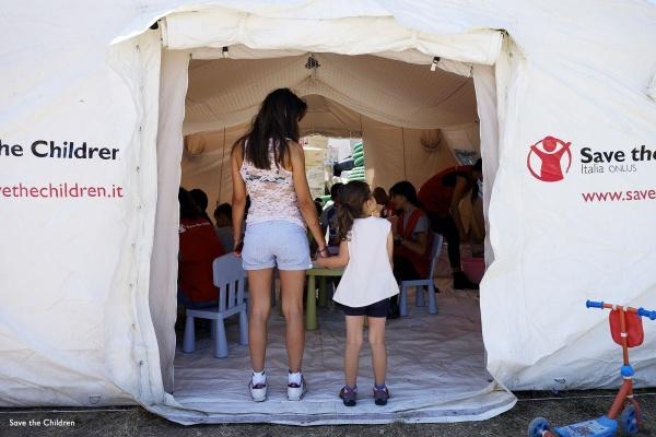 ragazza e bambina sull entrata di uno spazio a misura di bambino di save the children