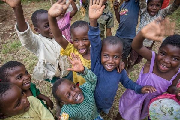 gruppo di bambini sorridenti con le mani alzate vestiti con diversi colori, foto dall'alto