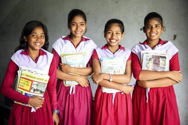 quattro bambine in piedi in divisa scolastica bianca e rosa