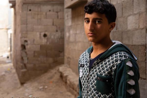 ragazzo palestinesi con capelli neri felpa blu notte e bianca davanti a un muro