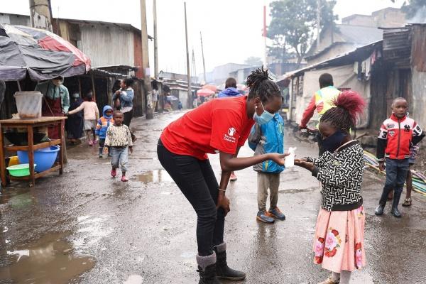 operatrice save the children con maglietta rossa e mascherina mentre assiste una bambina anch'essa con mascherina in una strada