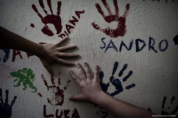 mani di bambini che appoggiate al muro disegnano la loro impronta colorata con la vernice