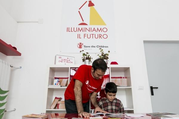 operatore save the children fa i compiti con un bambino nel punto luce