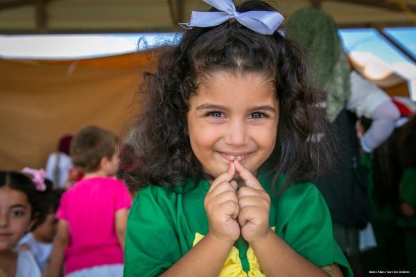 bambina con capelli castani vestita di verda e giallo tiene le mani davanti al viso mentre sorride