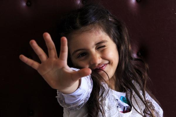 Bambina Siriana primo piano. Fa l'occhiolino e mostra la mano aperta.