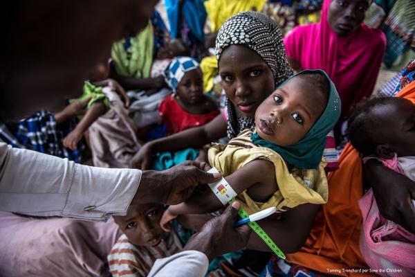mamma con il velo tiene in braccio la sua bambina mentre un operatore sanitario misura la conferenza del braccio della piccola per individuare o escludere una malnutrizione