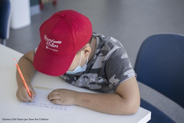 bambino alla scrivania che disegna con cappellino rosso