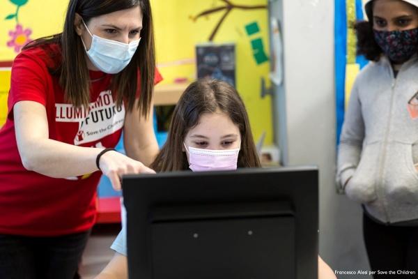 Bambina guarda il pc con operatrice Save accanto a lei