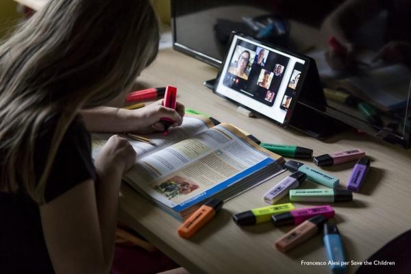 bambina seduta alla scrivania evidenzia un libro di scuola durante una lezione a distanza con tablet