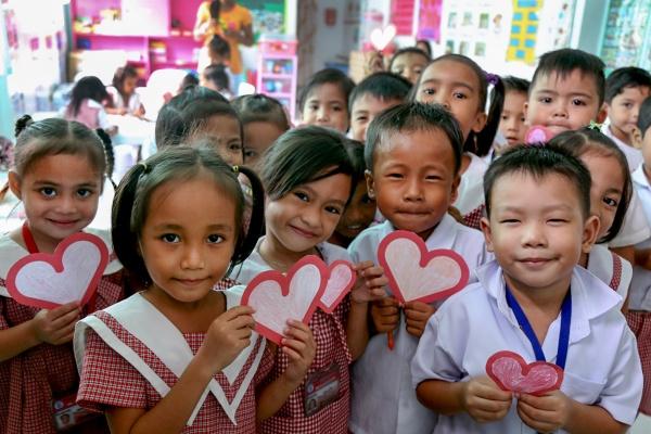 bambini orientali sorridono felici tenendo in mano dei cuoricini di carta