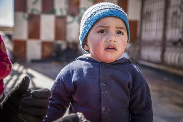 Bambino siriano mezzo busto triste in braccio al padre