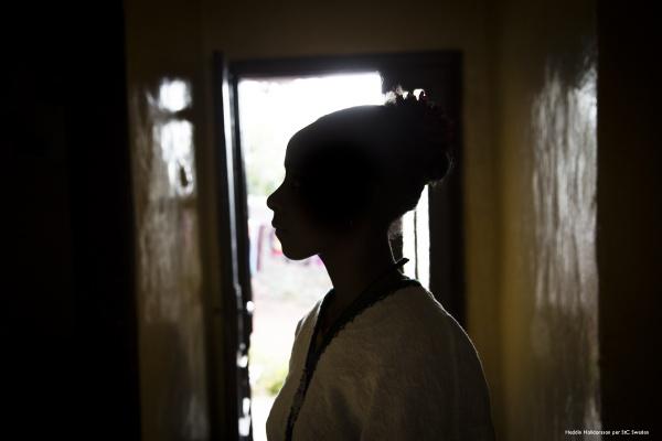 Sagoma ragazza con copricapo in testa foto di profilo in controluce.