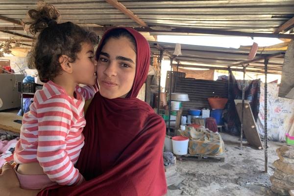 ragazza con velo rosso tiene in braccio una bimba con maglietta a righe bianca e rossa mentre si trovano un un allestimento temporaneo nei territori palestinesi occupati