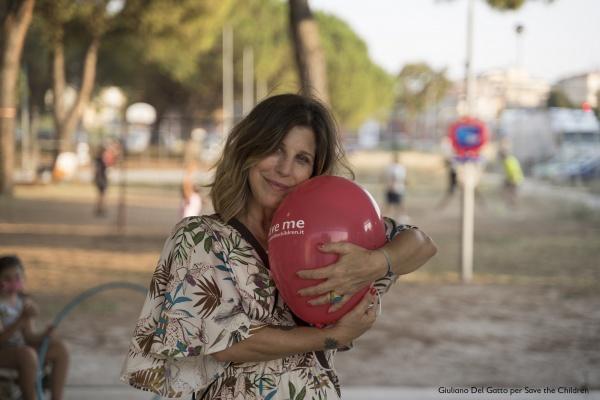 Michela Andreozzi in primo piano mentre abbraccia un palloncino rosso