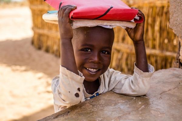 Bambino_africano_a_scuola_con_libri_sopra_la_testa_sorridente